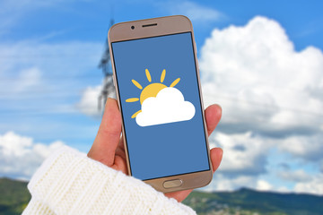Weather forecast concept with hand holding mobile phone with icon of cloud covering sun in front of blue sky with clouds in blurry background