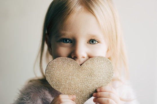 Valentines day. Little girl with a heart. Portrait of a little girl holding valentine's card.
