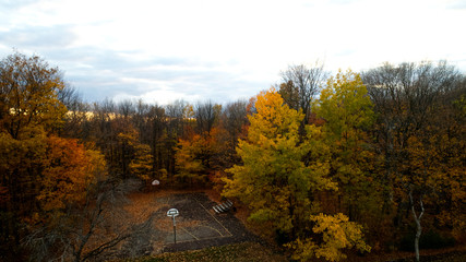 Aerial view of a playground surrounded by colorful forest in Autumn