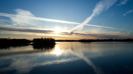 Aerial view of a sunset over the lake with white clouds made by planes