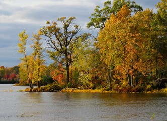 Lake shore by the river with a stormy sky in autumn