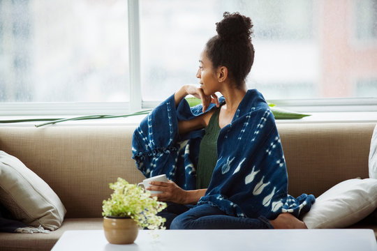 Thoughtful young female wrapped in blanket having coffee on sofa at home