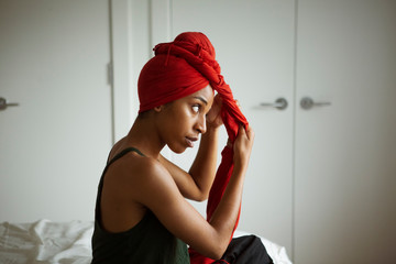 Young woman tying headscarf while sitting on bed at home