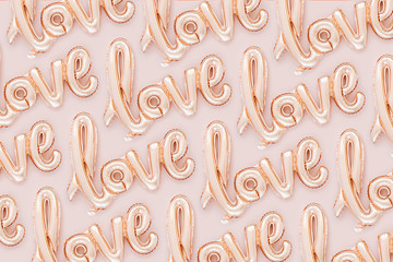 "Pale pink Foil Balloons in the shape of the word ""Love"" on pastel background. Love concept. Holiday, celebration. Valentine's Day or wedding/bachelorette party decoration."