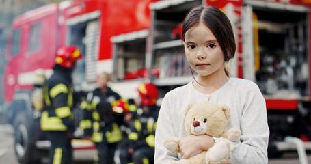 Portrait of saved little asian girl standing near fire truck. Firefighter in fire fighting operation