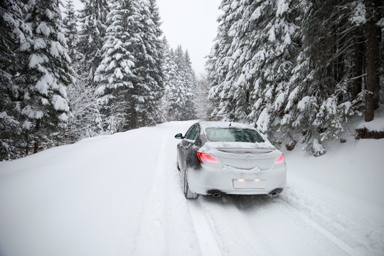 Driving a car on winter rural slippery roads.-Image