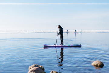 Attractive caucasian woman in black wetsuit paddle on SUP board with an oar. Female floating on stand up paddle board in the sea. In the background ice floes. Winter season and active leisure concept.