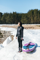 Pretty woman in black wetsuit stay on the coast and prepare to floating on SUP board. Girl enjoying the sun, on snow lies stand up paddle board. Female holds a thermo mug in her hand. Winter season.