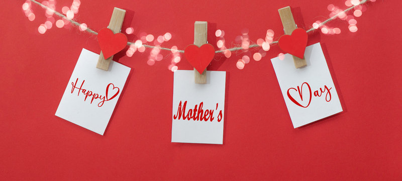 Happy Mother's Day background banner - White paper note hang on wooden clothes pegs with wooden hearts on a string isolated on red paper texture and bokeh lights, with space for text