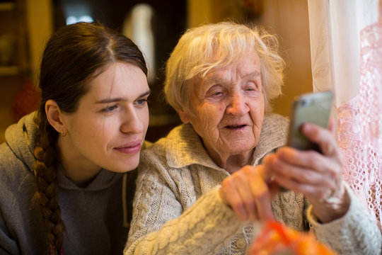 An elderly old woman looks at a smartphone his adult granddaughter.