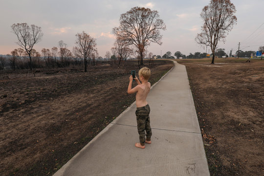 Young boy taking photos of aftermath of the 2019/2020 bushfire season in New South Wales, Australia