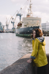 Attractive woman traveler in yellow raincoat walking in the port. Her hair flutters in the wind. Icebreaker and cranes at the background. Selective focus on girl. Vertical photo. Vacation concept.