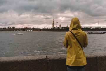 View from the back on a girl in yellow raincoat. Traveler admires of a Neva river and Peter and Paul fortress in Saint Petersburg. Dramatic landscape. Copy space. Tourism and vacation concept.