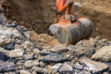A closeup and selective focus view on the broken up asphalt as a mini digger excavates earth in background, groundwork preparation for septic tanks