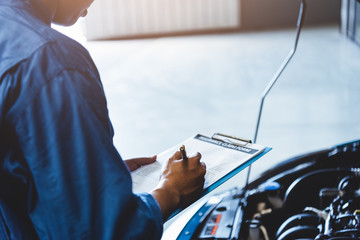 Car mechanic holding clipboard and checking to maintenance vehicle by customer claim order in auto...