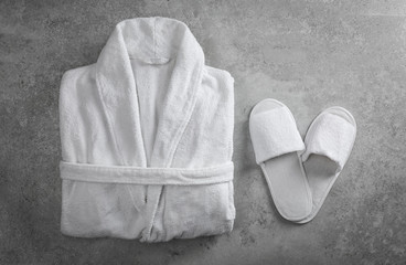 Clean folded bathrobe and slippers on grey stone background, flat lay