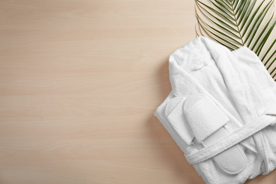 Clean folded bathrobe and slippers on wooden background, flat lay. Space for text