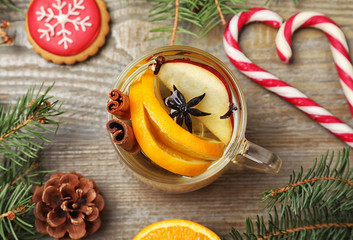 Aromatic mulled wine on wooden table, flat lay