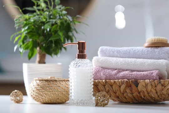 Soap dispenser, towels and brush on white table indoors