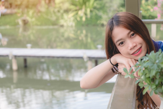 Beautiful young woman resting on bench, enjoy the sunlight outdoor in the park