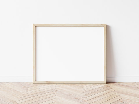 Horizontall wood frame mock up. Wooden frame poster on wooden floor with white wall. Landscape frame 3d illustrations.