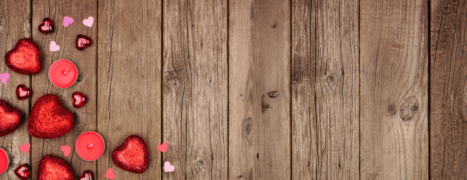 Valentines Day corner border banner with heart decorations and candles. Overhead view against a rustic wood background. Copy space.