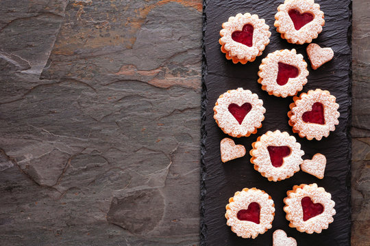 Valentines Day linzer jam cookies with heart shapes. Top view side border on a dark slate serving platter. Copy space.