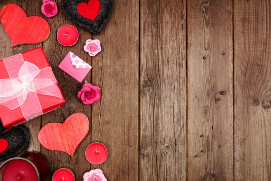 Valentines Day frame with red hearts, gifts and decor over a rustic wood background. Top view with copy space.