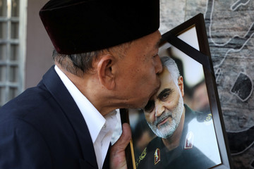 A man kisses a picture of Iranian Major-General Qassem Soleimani, who was killed in a airstrike near Baghdad, outside the Embassy of Iran in Kuala Lumpur
