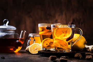 Poster Fleur Hot healing tea with ginger, honey, lemon and spices in glass cup, rustic wooden background copy space