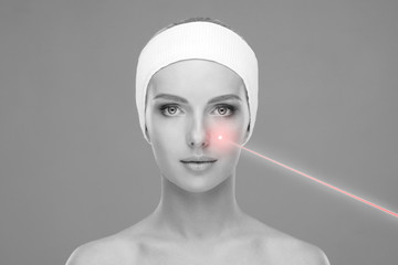 Doctor removing birthmarks with a laser ray. Beautiful face of a young woman. Mole removal, plastic surgery, skin lifting and aesthetic medicine.