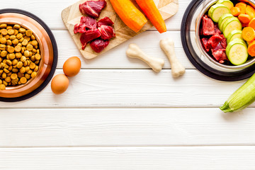 Ingredients of dry feed for dogs - meat, vegetables - near bones on white wooden background top-down copy space Wall mural