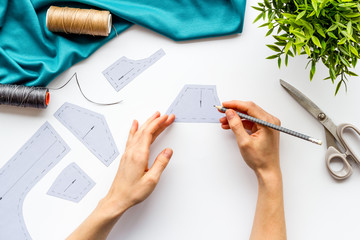 Tailor working. Women hands make patterns for clothes on white background top-down
