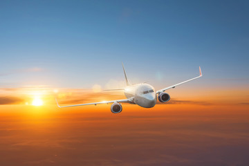 Plane flies at dawn high in the sky. Fotobehang