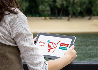 A woman is shopping at the online store. Shopping cart icon. Ecommerce.