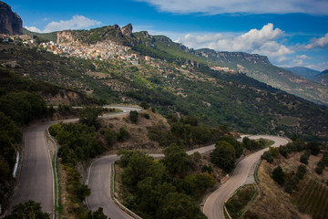 Twisty road leading to the historic city of Ulassai on the island of Sardinia. View of the rocky serrated mountains above the village. Fototapete