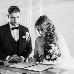 black and white photo. the bride and groom signing the marriage contract.