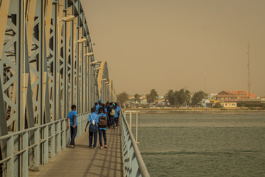 A group of kids from school is crossing a metal girder Faidherbe bridge in Sant Louis in senegal on a late sunny afternoon.