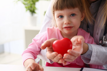 Little baby girl visiting doctor holding in hands red toy heart Fototapete