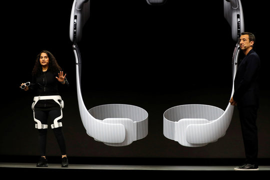 A woman demonstrates the Gait Enhancing & Motivating System, or GEMS, as Federico Casalegno, senior vice president and head of the Samsung Design Innovation Center, stands by during a Samsung keynote address at the 2020 CES in Las Vegas