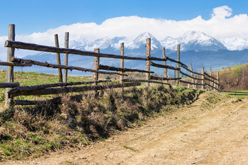 rural landscape in spring. composite landscape of mountain ridge in the distance with snow capped tops and fields with fence along the country dirt road. warm sunny weather