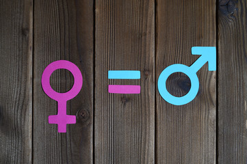 male and female symbols cut out of paper and an equal sign on a wooden background. the concept of gender equality