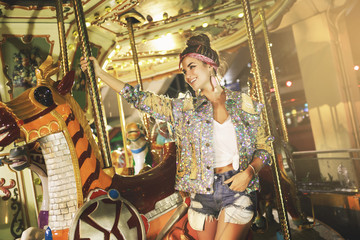 Stylish woman wearing sparkling jacket on the carousel