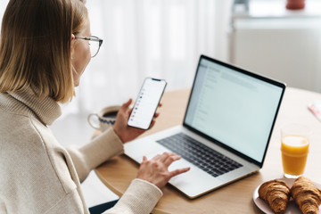 Photo of happy caucasian woman typing on laptop and cellphone