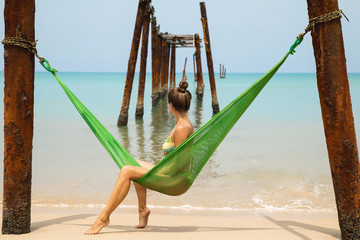Woman is relaxing in the hammock hanging on old beams from the broken pier