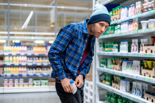 the kleptomania concept, a man in the grocery store stealing food and put it in the pocket