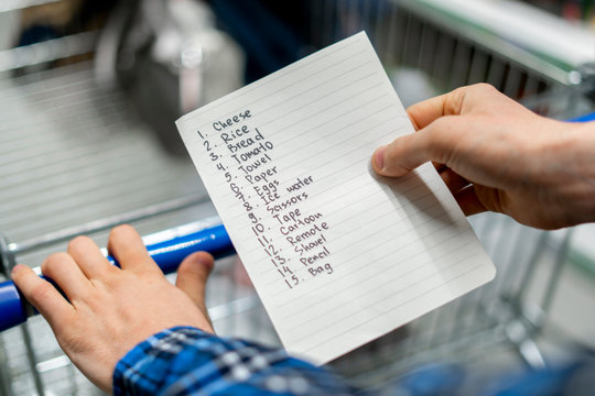 person's hands holding a shopping list paper sheet and check buying products in grocery store
