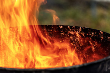 Close-up of flames in an old blackened metal bin