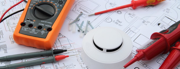 smoke detector with a screwdriver and a measuring device on a circuit diagram