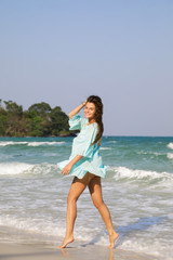 Young lovely woman is walking by the sea shore